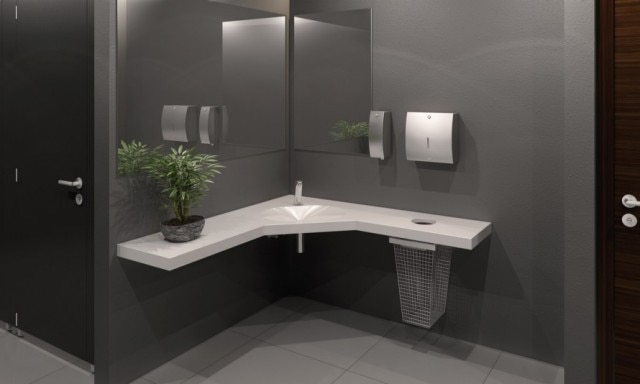 Office washroom with corner washbasin and stainless steel accessories